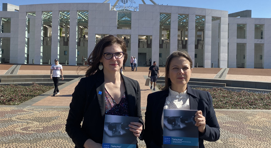 Two Human Rights Watch female staff members in front of Parliament House in Canberra holding their recently launched report entitled 'Fading Way'